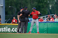 State College Spikes manager Jose Leon (19) argues a call with umpires Tyler Witte (left) and Jesse Busch (right) during a NY-Penn League game against the Batavia Muckdogs on July 2, 2019 at Dwyer Stadium in Batavia, New York.  Batavia defeated State College 1-0.  (Mike Janes/Four Seam Images)