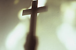 Shadow of hand holding large plain crucifix in front of blobs of light from church windows