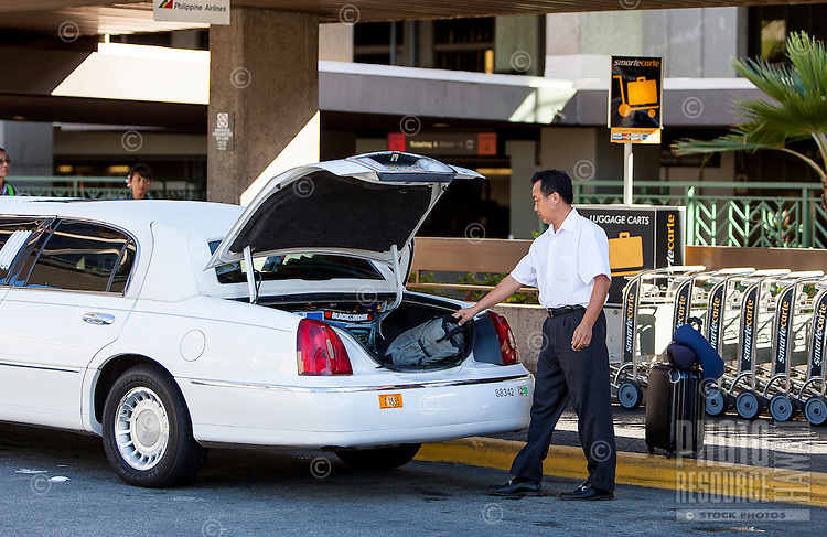 Local Asian limo taxi driver unloading luggage at the Honolulu International Airport, O'ahu