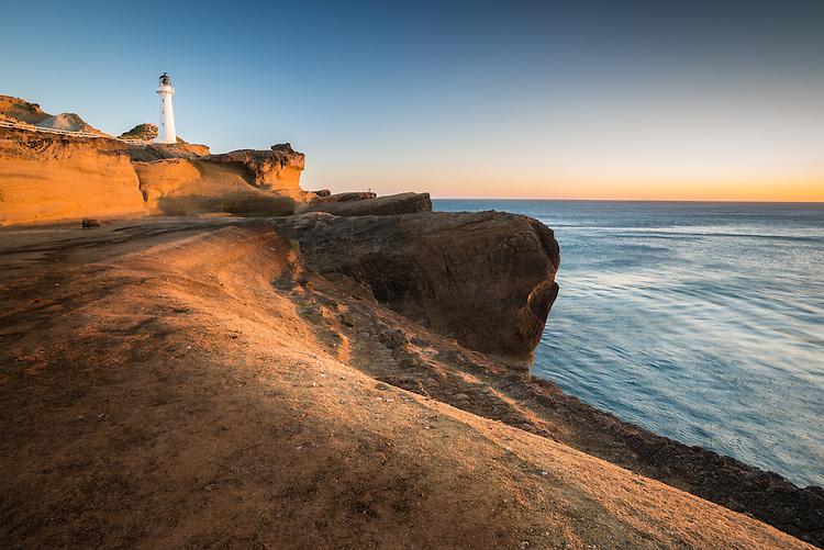 Sunrise lights the cliffs and lighthouse  at Castlepoint, Wairarapa Coast, New Zealand- stock photo, canvas, fine art print