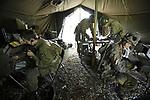 """Foto: VidiPhoto<br /> <br /> ARNHEM – Even was het dit weekend weer oorlog in Arnhem. Met een levensecht veldhospitaal en bijbehorende operaties, een verbindingstent voor radiocommunicatie, wapendemonstraties, een twintigtal reënactors van """"Five-Oh-Sink"""" en tal van andere bezienswaardigheden vierde het Arnhems Oorlogsmuseum 40-45 zijn 25-jarige bestaan. De (oefen)vijand liet het dit keer afweten. De Duitse 'troepen' kregen onderling ruzie, vochten hun eigen 'oorlog' uit en kwamen vervolgens niet opdagen, tot teleurstelling van museumeigenaar Eef Peeters. Daar tegenover stond de grote belangstelling van bezoekers uit het hele land."""