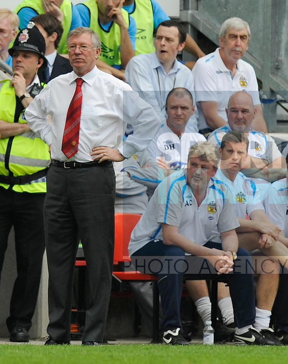 Sir Alex Ferguson manager of Manchester United stands while Steve Bruce Wigan Athletic manager sits behind during the Premier League match at The JJB Stadium, Wigan. Picture date 11th May 2008. Picture credit should read: Simon Bellis/Sportimage