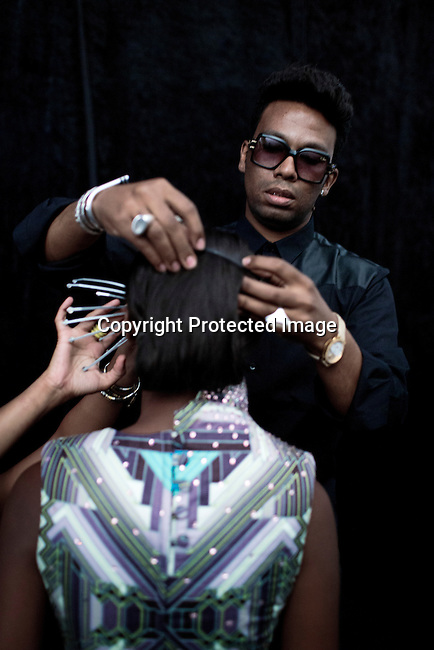 CAPE TOWN, SOUTH AFRICA MARCH 2: Designer David Tlale works on a piece of jewelry on a model backstage before a fashion show on March 2, 2014 in Cape Town, South Africa. Mr. Tlale is one of the most celebrated designers of South Africa and he showed a collection at Design Indaba Fair in Cape Town. (Photo by: Per-Anders Pettersson)