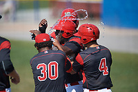 Batavia Muckdogs designated hitter Lazaro Alonso (19) is mobbed by teammates, including Edward Cabrera (30) and Michael Hernandez (4) after scoring the game winning run on a bases loaded walk during the first game of a doubleheader against the Williamsport Crosscutters on August 20, 2017 at Dwyer Stadium in Batavia, New York.  Batavia defeated Williamsport 6-5.  (Mike Janes/Four Seam Images)