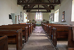 Wooden pews, altar, and east window with undivided nave and sanctuary inside the church at Easton Royal, Wiltshire, England built in 1591