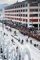 Spectators line the streets of 4th avenue as they watch Noah Pereira run down the trail after leaving the start line during the Ceremonial Start of the 2016 Iditarod in Anchorage, Alaska.  March 05, 2016