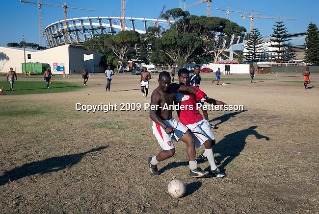 CAPE TOWN, SOUTH AFRICA MARCH 11: Construction workers practice soccer after work next to the Green Point stadium on March 11, 2009 in Cape Town, South Africa. The stadium will be used for the 2010 World Cup Soccer tournament held in South Africa in June 2010. About 1500 workers work at the stadium and the seat capacity will be abut 68 000. It will have a retractable roof. (Photo by: Per-Anders Pettersson/Getty Images)...
