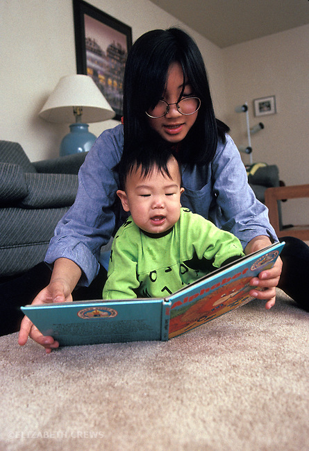 Palo Alto CA Preteen Japanese girl entertaining baby brother, eight-months-old by showing him a book