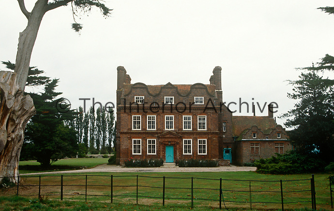 A turquoise front door strikes a colourful note on the facade of this Jacobean house