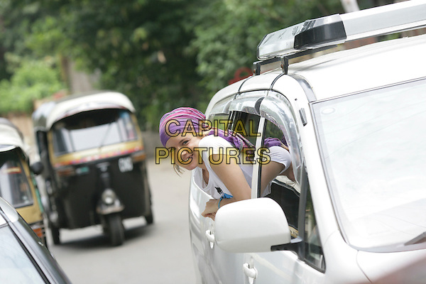 SIENNA MILLER.Global Cool Ambassador Sienna Miller in India with the campaign to help reduce carbon emissions..19th July 2007 Mumbai, India.half length car purple bandana leaning out of window.CAP/CAM.©Andre Camara/Capital Pictures