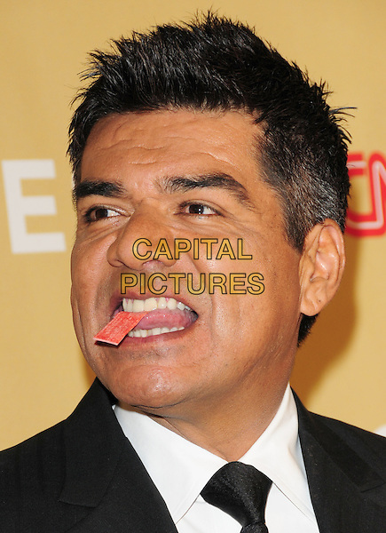GEORGE LOPEZ .at The 3rd Annual CNN Heroes: An All-Star Tribute held at The Kodak Theatre in Hollywood, California, USA,  November 21st 2009                                                                   .portrait headshot gum paper ticket in mouth open funny black tie white shirt .CAP/RKE/DVS.©DVS/RockinExposures/Capital Pictures