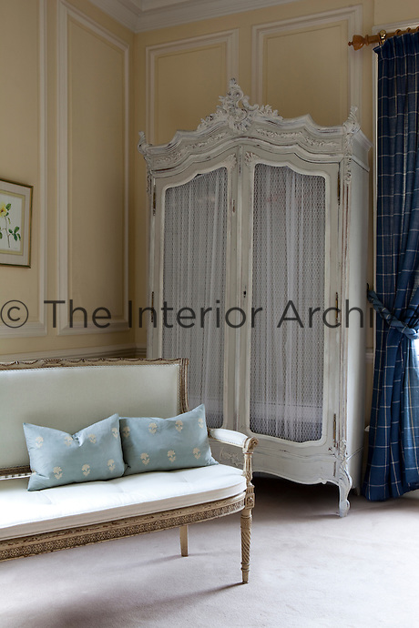 An antique French armoire stands in the corner of a bedroom. A French settee stands in front