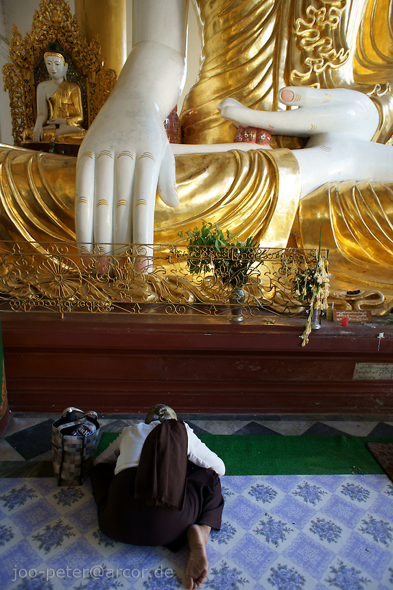 Devotee prays in front of big Buddha sculpture in the back of the congregation hall in Shwedagon pagoda complex, Yangon, Myanmar, 2011