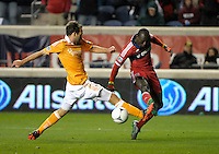 Houston midfielder Adam Moffat (16) lunges to prevent a shot by Chicago forward Dominic Oduro (8). The Houston Dynamo defeated the Chicago Fire 2-1 in the Eastern Conference play-in game for the MLS Playoffs at Toyota Park in Bridgeview, IL on October 31, 2012.