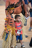 An indigenous Bororo boy wearing ceremonial feather headdress and palm skirt puts his arm on the shoulder of a younger Brazilian boy with a face paint design on his cheek at the International Indigenous Games, in the city of Palmas, Tocantins State, Brazil. Photo © Sue Cunningham, pictures@scphotographic.com 27th October 2015