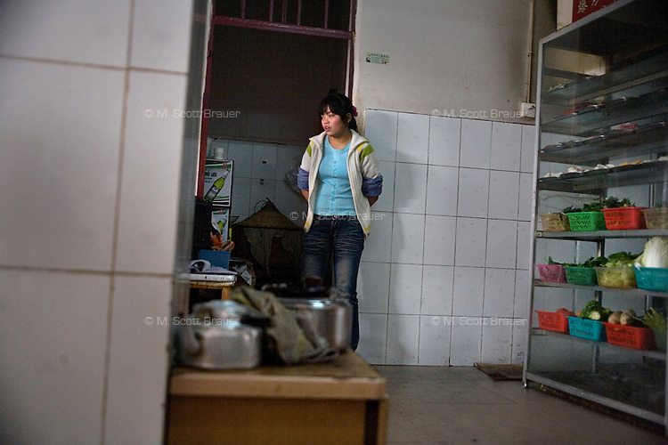 The waitress in a small restaurant takes a break near the kitchen between serving customers in Kunming, Yunnan Province, China.