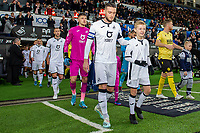 Matt Grimes of Swansea City walks out with a mascot during the Sky Bet Championship match between Swansea City and Millwall at the Liberty Stadium in Swansea, Wales, UK. Saturday 23rd November 2019