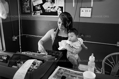 North Carolina<br /> September 2011<br /> <br /> A young woman holds her niece as she works the cash register at her parents restaurant.