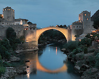 Stari Most or Old Bridge at night, a 16th century Ottoman bridge across the Neretva river in Mostar, Bosnia and Herzegovina. The bridge was destroyed in the 1990s Yugoslavian war and has been rebuilt. The town is named after the mostari or bridge keepers of the Old Bridge. Mostar developed in the 15th and 16th centuries as an Ottoman frontier town and is listed as a UNESCO World Heritage Site. Picture by Manuel Cohen