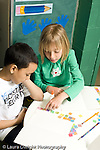 Education Elementary school Grade 1 mathematics hands on learning boy and girl using colored squares to understand concept gluing them to paper vertical