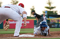 Brian Rike (14) of the Tulsa Drillers slides safely back into first base during a game against the Springfield Cardinals at Hammons Field on July 19, 2011 in Springfield, Missouri. Tulsa defeated Springfield 17-11. (David Welker / Four Seam Images)