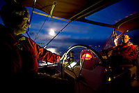 Crew of a cruising sailboat on watch at night, during a Pacific crossing