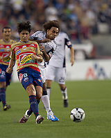 Monarcas Morelia defender Fernando Salazar (13) passes the ball as New England Revolution defender Kevin Alston (30) pressures. Monarcas Morelia defeated the New England Revolution, 2-1, in the SuperLiga 2010 Final at Gillette Stadium on September 1, 2010.