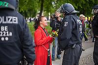 """Am Samstag den 16. Mai 2020 demonstrierten in Berlin an mehreren Orten mehrere hundert Menschen mit sog. """"Hygiene-Demonstrationen"""" gegen die Einschraenkungen zur Eindaemmung der Covid-19-Pandemie. An diesen """"Hygiene-Demonstrationen"""" nahmen vor allem Verschwoerungsanhaenger aber auch Hooligans, Neonazis und andere Rechte teil.<br /> Im Bild: Polizeibeamte haben eine ungenehmigte Demonstration von bis zu 500 Menschen zu gestoppt. Eine Demonstrationsteilnehmerin versucht Rosen an Polizeibeamte zu verteilen.<br /> 16.5.2020, Berlin<br /> Copyright: Christian-Ditsch.de<br /> [NUR FUER REDAKTIONELLE ZWECKE! Werbung nur auf Anfrage beim Fotografen. Inhaltsveraendernde Manipulation des Fotos nur nach ausdruecklicher Genehmigung des Fotografen. Vereinbarungen ueber Abtretung von Persoenlichkeitsrechten/Model Release der abgebildeten Person/Personen liegen nicht vor. NO MODEL RELEASE! Don't publish without copyright Christian-Ditsch.de, Veroeffentlichung nur mit Fotografennennung, sowie gegen Honorar, MwSt. und Beleg. Konto: I N G - D i B a, IBAN DE58500105175400192269, BIC INGDDEFFXXX, Kontakt: post@christian-ditsch.de<br /> Bei der Bearbeitung der Dateiinformationen darf die Urheberkennzeichnung in den EXIF- und  IPTC-Daten nicht entfernt werden, diese sind in digitalen Medien nach §95c UrhG rechtlich geschuetzt. Der Urhebervermerk wird gemaess §13 UrhG verlangt.]"""