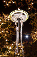 Nighttime scene of Seattle Space Needle and full moon through branches decorated with Christmas lights, Seattle Center, Seattle, Washington, US