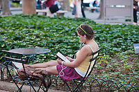 A reader uses her Amazon Kindle electronic book in Bryant Park in New York on Thursday, May 31, 2012. (© Richard B. Levine)