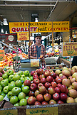 CANADA, Vancouver, British Columbia, young man sells apples at the Granville Island Public Market