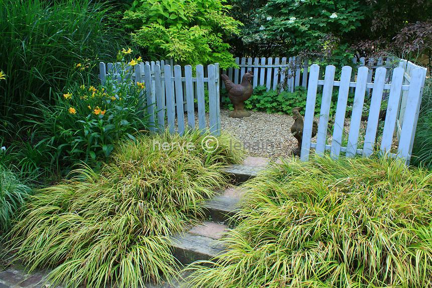 Jardins du pays d'Auge (mention obligatoire dans la légende ou le crédit photo) : devant le poulailler, espace clos de barrières bleues et escalier bordée d' Acorus gramineus 'Ogon'.