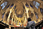 St. Patrick's Cathedral before Mass, with woman praying in pews and fisheye view of main alter and domed roof, Manhattan, NYC, NY, USA, June 27, 2011