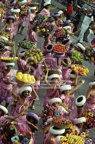 Rio de Janeiro, Brazil. Carnival samba school; sambistas carrying baskets of fruit, wearing pink.