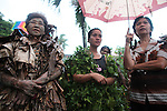 "A trio of women sing hymns during the annual Taong Putik, or ""mud people,"" festival in Bibiclat, on Luzon island,  Philippines. The festival honors St. John the Baptist, and devotees cover themselves in mud and vines to symbolize the animal skins he wore in the Bible. The festival draws old and young alike, most of whom wear the ritual dress, while others wear a modified version or none at all. June 24, 2011."