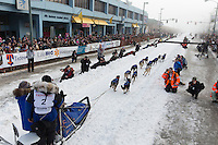 Martin Buser runs down 4th avenue at the ceremonial start of the Iditarod sled dog race in downtown Anchorage Saturday, March 2, 2013. ..Photo (C) Jeff Schultz/IditarodPhotos.com  Do not reproduce without permission