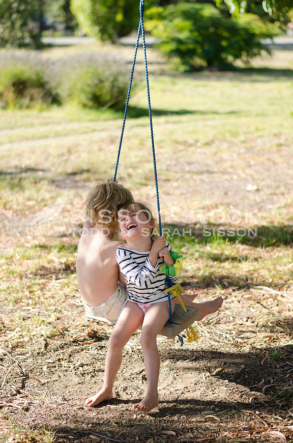 Young girl smiling and sharing a rope swing with young boy on a summers day, New Zealand - stock photo, canvas, fine art print