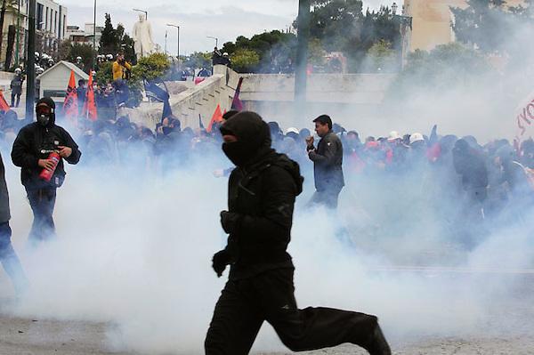 ARA09. ATENAS (GRECIA), 23/02/2011.- Policía antidisturbios ganzan gases lacrimógenos a protestantes durante los enfrentamientos entre grupos de radicales y las fuerzas de orden ocurridos en la manifestación convocada con motivo de la huelga general contra la rígida política de ahorro del Gobierno, en el centro de Atenas, Grecia, el 23 de febrero de 2011. EFE/Simela Pantzartzi