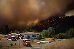 Firefighters protect an evacuated home while the Sand Fire burns behind it near Plymouth, California, July 26, 2014. <br /> The Sand Fire destroyed 20 homes and burned more than 4,200 acres near the town of Plymouth.