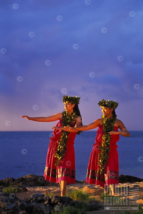Two young women dancing kahiko (ancient) hula wearing maile leis  near ocean