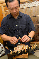 "Takashi Fujita, ""Awatake Ningyo"" bamboo figure artist, working on a figure, Naruto, Tokushima Prefecture, Japan, July 8, 2014. The city of Naruto in Tokushima Japan is famous for whirlpools that form in the Naruto Strait. It is home to Otani pottery and the first two temples on the Shikoku 88 temple pilgrimage."