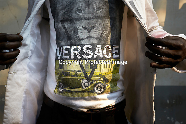 """KINSHASA, DEMOCRATIC REPUBLIC OF CONGO - July 16: A Sapeur from the group Leopard de la Sape shows his Versace designer label clothes on July 16, 2014, in Kinshasa, DRC. The word Sapeur comes from SAPE, a French acronym for Société des Ambianceurs et Persons Élégants  or  Society of Revellers and Elegant People  and it also means,  to dress with elegance and style"""". Most of the young Sapeurs are unemployed, poor and live in harsh conditions in Kinshasa, a city of about 10 million people. For many of them being a Sapeur means they can escape their daily struggles and dress like fashionable Europeans. Many hustle to build up their expensive collections. Most Sapeurs could never afford to visit Paris, and usually relatives send or bring clothes back to Kinshasa. (Photo by Per-Anders Pettersson)"""