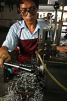 Worker cuts metal with a lathe at a factory in Zhouqing, Guangdong Province, China. The factory makes promotional gift items..06 May 2005