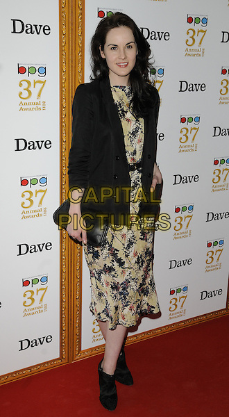 MICHELLE DOCKERY.The Broadcasting Press Guild TV & Radio Awards, Theatre Royal, Drury Lane, London, England..March 25th, 2011.full length black blazer blue yellow floral print dress hand in pockets clutch bag ankle boots  .CAP/CAN.©Can Nguyen/Capital Pictures.