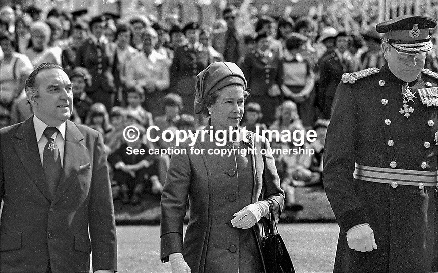 Queen Elizabeth II, in the grounds of Government House, Hillsborough, Co Down, during her Silver Jubilee visit to N Ireland. She is accompanied by Roy Mason, Secretary of State for N Ireland, left, and General Sir John d'Arcy Anderson, Colonel Commandant, Ulster Defence Regiment. 197708100074c<br />