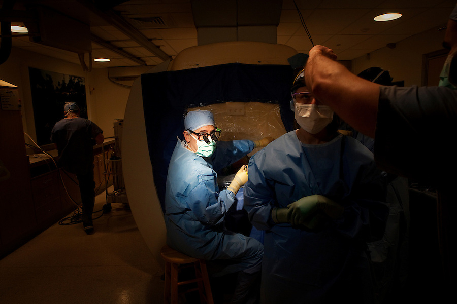 San Francisco, California, January 6, 2011 - University of California San Francisco Medical Center neurosurgeon Dr. Philip Starr (left) prepares to drill into the skull patient Linda Sharp while clinical fellow Dr. Ellen Air has her headlamp adjusted during an iMRI surgery at UCSF Medical Center. The MRI machine photographs the patient during the surgery allowing the doctors operating to view the procedure as well as support doctors and technicians to monitor from an outside room.  The iMRI procedure uses Deep brain stimulation (DBS), which has been used for over a decade to treat movement disorders such as Parkinson's disease, essential tremor, and dystonia. DBS uses a pulse generator implanted in the chest, similar to a pacemaker, to deliver pulses to specific regions of the brain via a permanently implanted electrode. In the U.S., DBS is normally done while the patient is awake, because the surgeon needs to induce the symptoms (like the involuntary movements of Parkinson's) to know if he's in the right place, and if the patient is unconscious, the symptoms can't be induced. Many patients find it hard to tolerate. Their head is clamped in a frame, they're aware of their surroundings, and the surgeon is deliberately producing tremors and twitches while they lie there...Interventional MRI (or iMRI) allows surgeons to implant these electrodes while the patient is unconscious taking advantage of MR imaging in real time by performing procedures inside the scanner itself. Doctors Paul Larson and Philip Starr were both involved with this technology during its development in the 1990s. In 2002 they began to think about how to perform DBS using this technique at UCSF. Working with Alastair Martin PhD in the Department of Radiology, Jill Ostrem MD in the Department of Neurology, and others, they developed a technique of implantation using a modified but commercially available skull-mounted aiming device and custom-made, MR-compatible surgical instruments.
