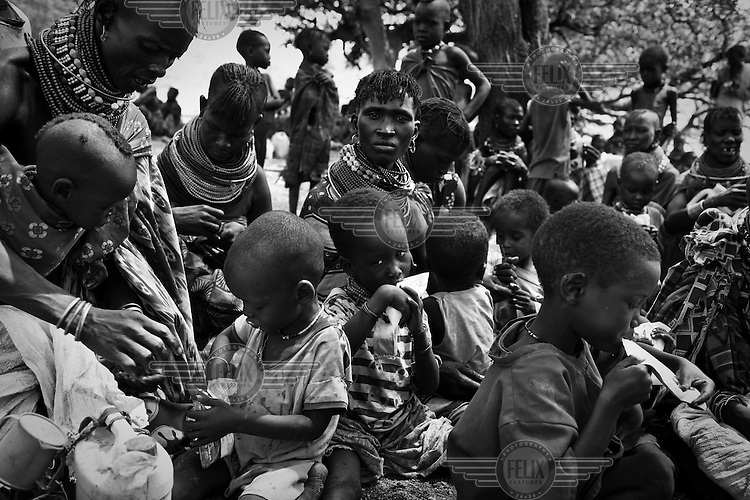 A group of Turkana women feed their malnourished children with packets of plumpy nut as part of the out reach programme organised by Merlin NGO in Nakapelewoi village.