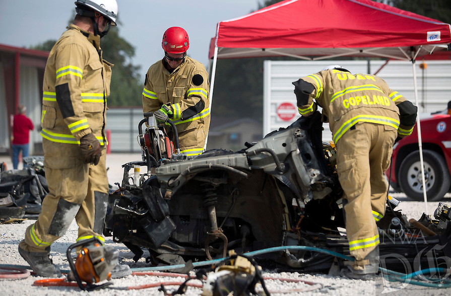 NWA Democrat-Gazette/JASON IVESTER<br /> Rogers Fire Department special operations personnel were working on Thursday, Sept. 8, 2016, in three-man rotations competing against the clock to strip the car down into pieces small enough to pass through a 22.5&quot; tire. The competition allows them to better learn their tools as well as vehicular construction to assist them in extrications.