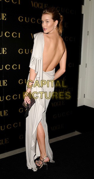 ROSIE HUNTINGDON-WHITELEY.A dinner in honour of Frida Gianni, Creative Director of Gucci, hosted by Alexandra Shulmanand at the Saatchi Gallery, Duke of York's Headquarters, King's Road, Chelsea, London, England..April 1st, 2009 .Vogue full length white dress grey gray silver silk satin  long maxi looking over shoulder backless one shoulder clutch bag.CAP/CAN.©Can Nguyen/Capital Pictures.