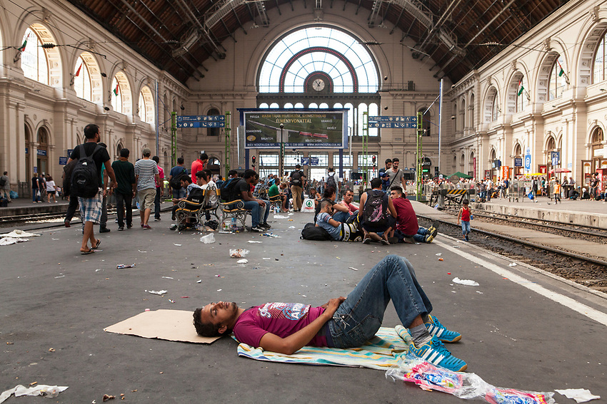 A young Syrian refugee sleeps alone on the main platform of the Budapest Railway station. Mostly Syrian refugees seek rest while waiting for trains to take them away to destinations around Europe. The Hungarian government closed the station and then reopened but cancelled all international trains. Budapest Keleti railway station  is the main international and inter-city railway terminal in Budapest, Hungary.